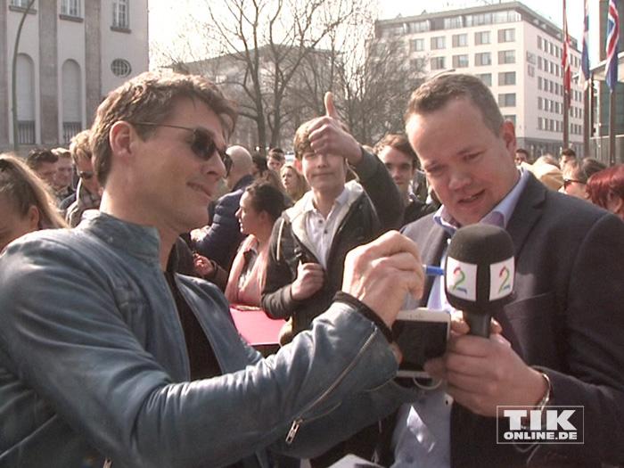 Ein Reporter bekommt von Morten Harket ein Autogramm auf sein Mikrofon