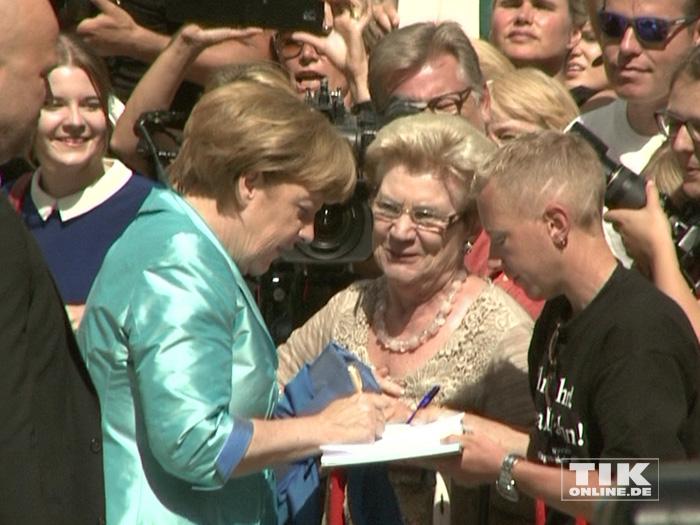 Kanzlerin Angela Merkel zeigte sich bei den Bayreuther Festspielen 2015 volksnah und schrieb Autogramme