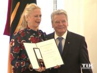 Zwinker: Eine sichtlich stolze Barbara Schöneberger posiert mit ihrem Bundesverdienstkreuz neben Bundespräsident Joachim Gauck