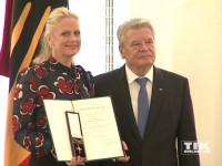 Barbara Schöneberger strahlt glücklich mit ihrem Bundesverdienstkreuz neben Bundespräsident Joachim Gauck