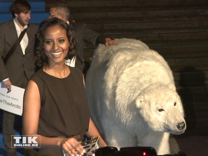 Ein wenig ratlos lacht Topmodel Sara Nuru, als ein lebensgroßer Plüsch-Eisbär als Teil einer Protestaktion für den Schutz der Arktis bei der Cinema for Peace Gala 2015 über den roten Teppich trottet.