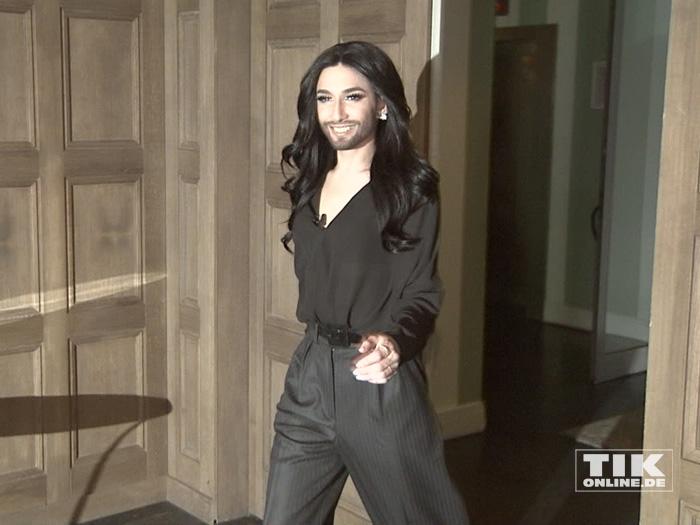 Conchita Wurst erschien mit schwarzer Bluse, dunkelgrauer Hose, Wallemähne und ihrem Markenzeichen, dem Dreitagebart.