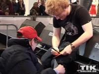 Sänger Ed Sheeran gibt als erstes einem Rollstuhlfahrer ein Autogramm und setzt sich sogar zu ihm herunter