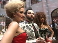 Harald Glööckler posiert mit Models, die er in Servietten-Kleider gesteckt hat