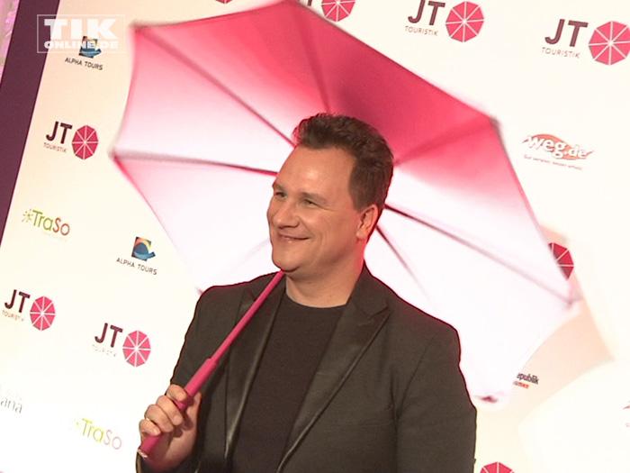 Guido Maria Kretschmer posiert mit Sonnenschirm