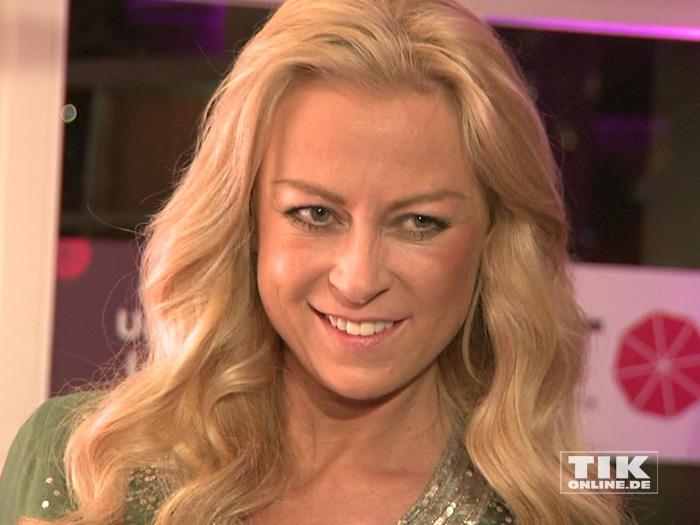 Jenny Elvers lächelt etwas gequält in die Kameras