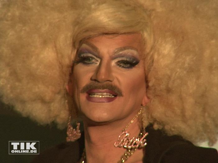 Kult-Transe Gloria Viagra mit ihren Markenzeichen Schnauzbart und blonder Pudelfrisur