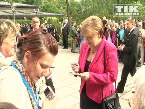Bundeskanzlerin Angela Merkel schreibt Autogramme