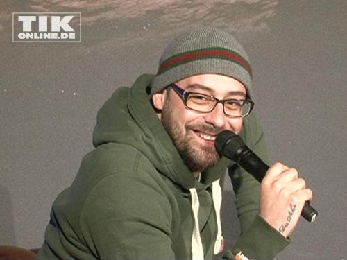 Sido strahlt mit Mütze und Brille in die Kameras
