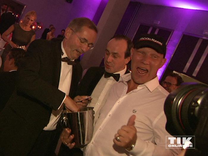 Axel Schulz verteilt Lose an Matthias Platzeck bei der TULIP Parkinson Gala 2015 in Berlin