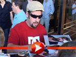 Adam Sandler und Rob Schneider schreiben vor dem Hotel in Berlin Autogramme