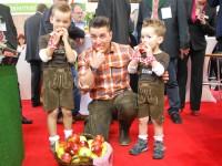 Andreas Gabalier und zwei kleine Lederhosen-Träger lassen sich Äpfel schmecken