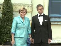 Kanzlerin Angela Merkel posiert in einem türkisen Kostüm neben ihrem Ehemann Joachim Sauer bei den Bayreuther Festspielen 2015 für die Fotografen
