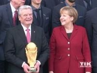 Joachim Gauck und Angela Merkel strahlen mit dem WM-Pokal