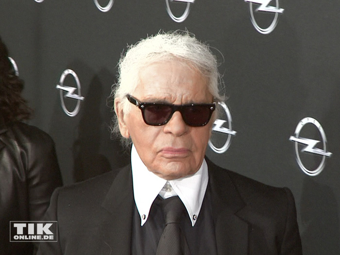 Karl Lagerfeld wie man ihn kennt: Zupf, Sonnenbrille, hochgeschlossenes weißes Hemd und schwarzer Anzug