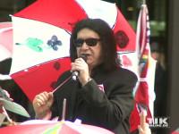"""Stolz trägt KISS-Bassist Gene Simmons einen """"Regenschirm für den Frieden"""", der von Kindern einer Berliner Grundschule bemalt wurde"""
