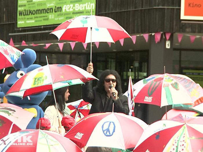 """KISS-Bassist Gene Simmons umringt von """"Regenschirmen für den Frieden"""", die von Kindern einer Berliner Grundschule bemalt wurde"""