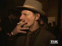 Alexander Scheer mit Hut und selbst gedrehter Zigarette auf der Medienboard-Weihnachts-Party 2015 in Berlin