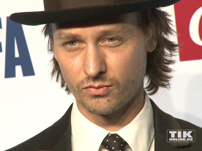 Tom Schilling posiert mit Hut bei der Opening Night Gala der 66. Berlinale