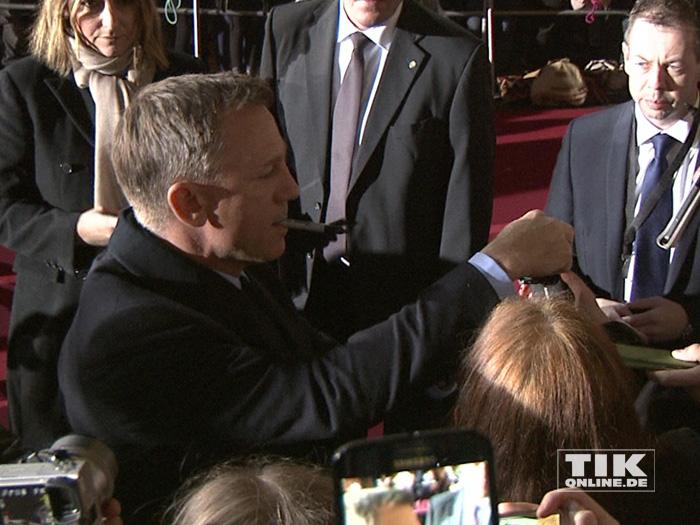 """Mit dem Stift im Mund knipste Daniel Craig bei der """"James Bond - Spectre""""-Premiere in Berlin Fotos mit den wartenden Fans"""