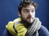 """Schauspieler Roland Zehrfeld präsentiert sich mit einem Schal aus der Aktion """"Ein Schal fürs Leben"""" zu Gunsten der Organisation """"Save the Children"""""""