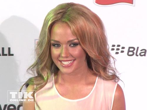 """Kim """"Gloss"""" Debkowski lächelt beim Music Meets Media 2013 für die Kameras"""