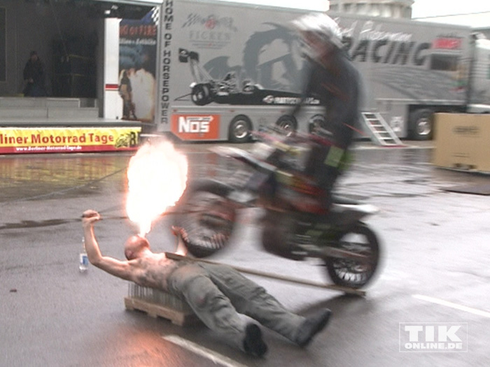 """Stuntman Sebastian """"Satu"""" Kopke liegt auf einem Nagelbrett, spuckt Feuer und lässt ein Bike über sich hinwegbrausen beim Warm up der Berliner Motorrad Tage BMT 2016"""