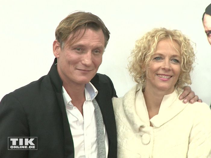 """Hauptdarsteller Oliver Masucci und Katja Riemann posieren Arm in Arm auf der Premiere von """"Er ist wieder da"""" in Berlin"""